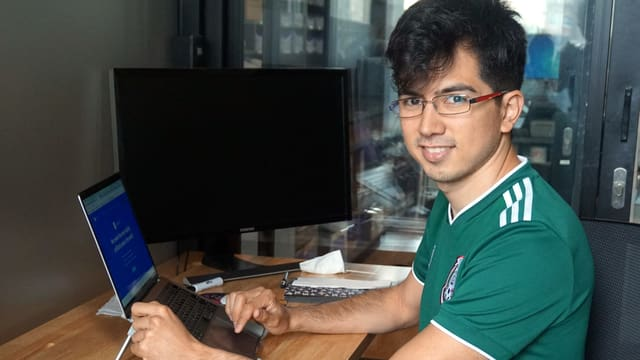 Ein junger Mann mit einem Fussballtrikot, dunklen Haaren und einer Brille sitzt vor einem Laptop.