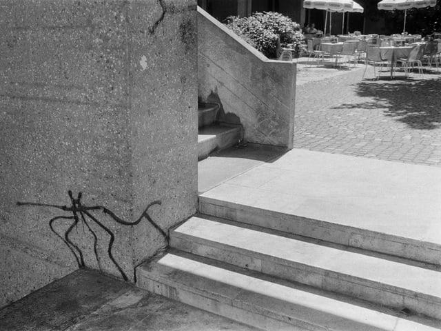 Eine Strichfigur neben einer Treppe.
