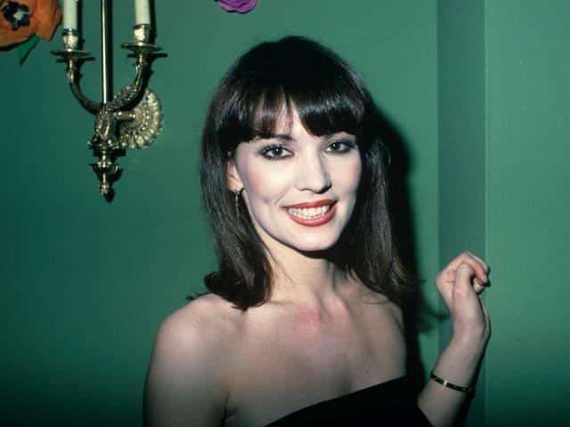 Bild von Iris als sie jung war. Sie steht vor einer grünen Wand und lächelt. Sie trägt einen schwarzen Pony, roten Lippenstift und dunkles Augen-Make-up.