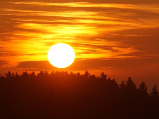 Ein leuchtender Feuerball am roten Himmel.