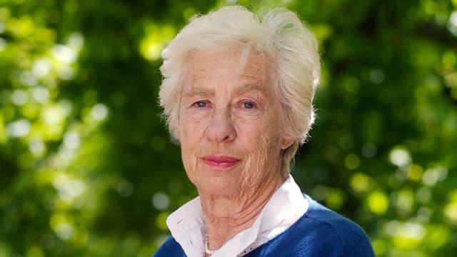 Eine ältere Frau mit weissem Kragen und blauem Pulli.