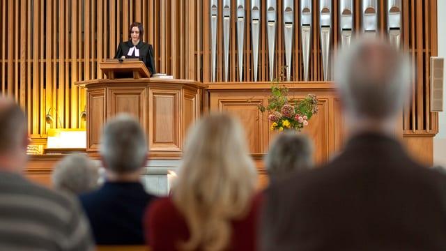 Kirchenraum mit Pfarrerin, Orgel und Kirchgängern