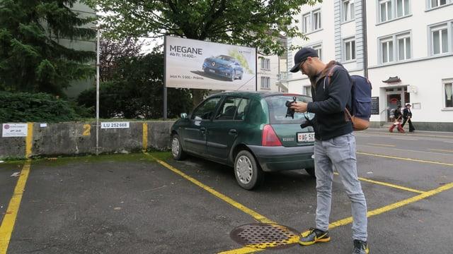 Ein Mann mit Kappe fotografiert einen Guilldeckel auf einem Parkplatz.