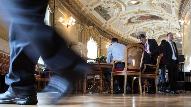 Menschen stehen rund um einen Tisch in der Wandelhalle im Bundeshaus in Bern