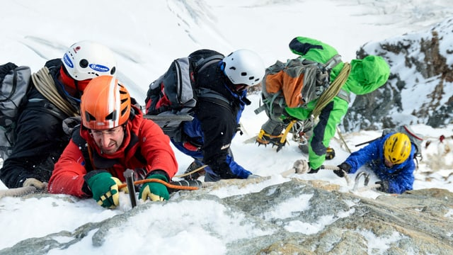 Bergsteiger in Fels und Eis beim gefährlichen Abstieg.