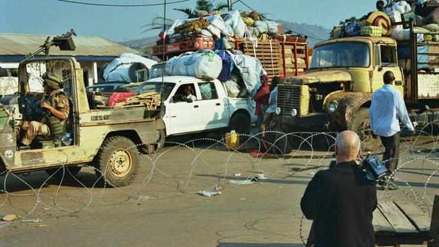 Überladene Autos und Trucks in einer afrikanischen Gegend.