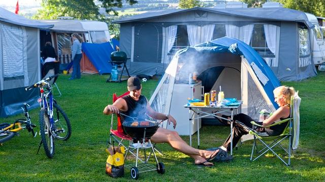Paar grilliert vor dem eigenen Zelt