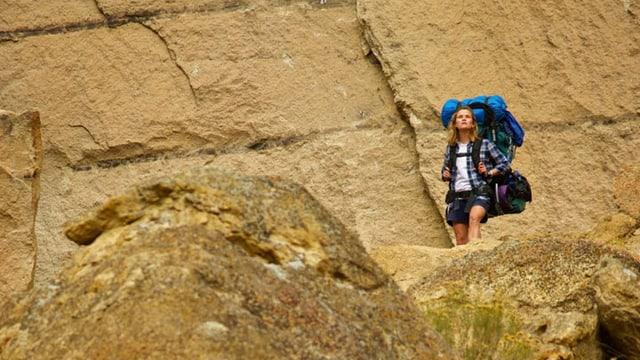 Reese Witherspoon mit riesigem Rucksack vor grosser Felswand.