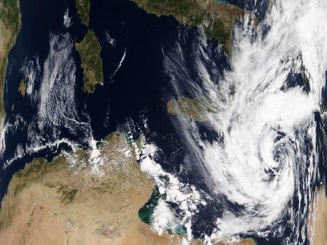 Ein Satellitenbild zeigt das Mittelmeer mit einem wirbelförmigen Wolkenband.