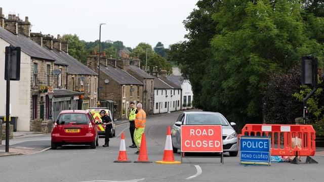 Strasse in ein Dorf. Sie ist abgesperrt. Auf einem Schild steht: Road Closed.