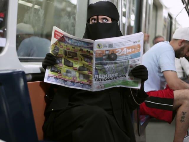 Ein Frau in Burka sitzt in einer U-Bahn und liest Zeitung