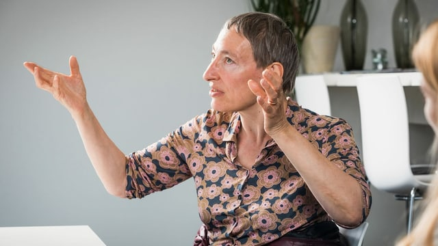 Eine Frau mit kurzen grauen Haaren und Blumenbluse gestikuliert mit beiden Händen.