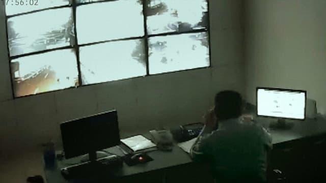 Aufnahme einer Überwachungskamera: ein Mann sitz an einem Bürotisch und schaut auf mehrere Bildschirme