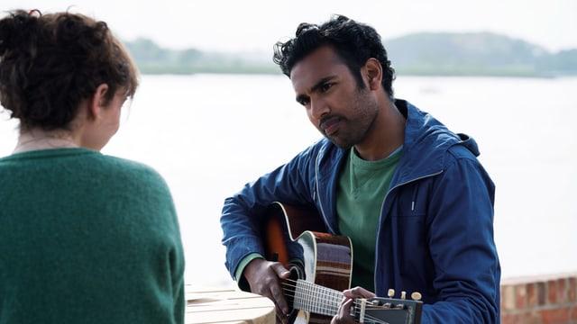 Ein Mann spielt am Strand Gitarre, eine Frau schaut ihm dabei zu.