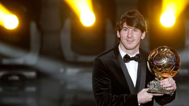 Lionel Messi hält den Ballon d'Or in den Händen.