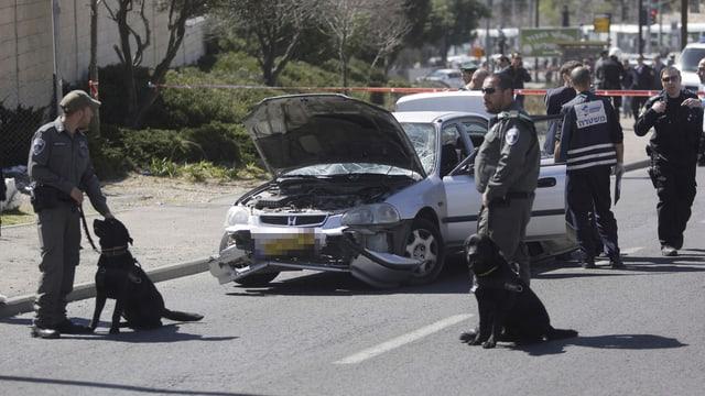 Sicherheitsleute bewachen  das Auto, das in Jerusalem in eine Menschenmenge gefahren ist.
