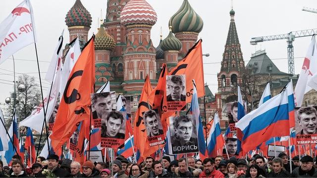 Menschen mit russischen und anderen Flaggen sowie Bildern von Nemzow vor dem Kreml.