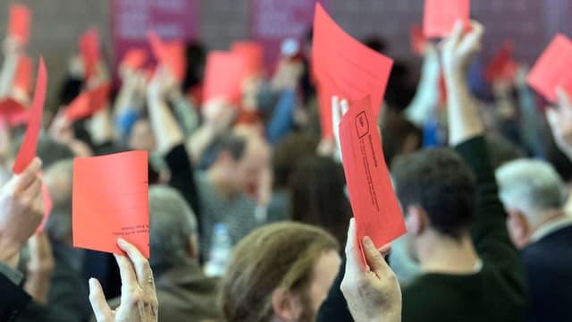 Personen mit roten Stimmzetteln in die Höhe haltend.