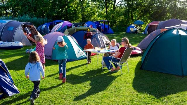 Kinder zwischen Zelten.