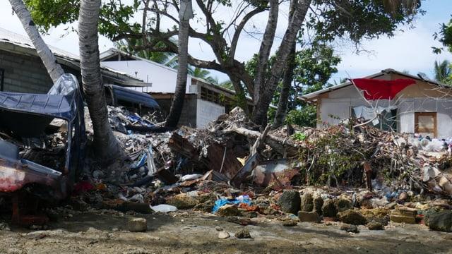 Müll und ein Autowrack vor Häusern.
