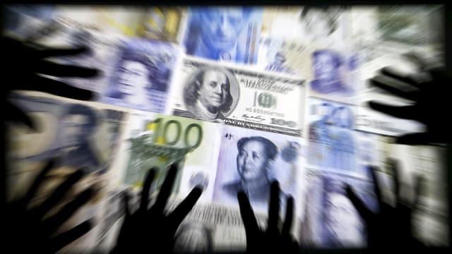 Symbolbild: Hände greifen nach Banknoten verschiedenster Währung.
