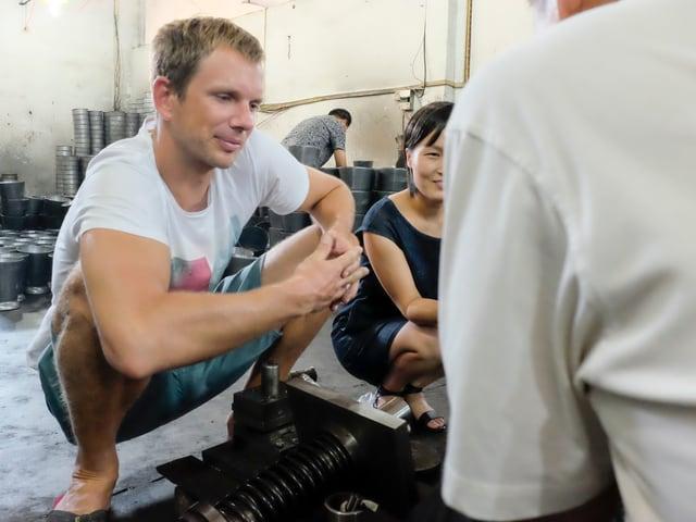Ein Schweizer und eine Chinesin  sprehcen mit einem Mann.
