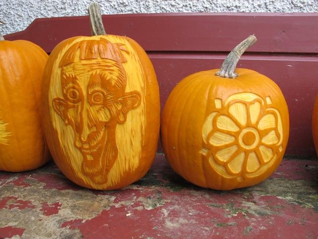 Zwei geschnitze Kürbisse mit Gesicht und Blume.