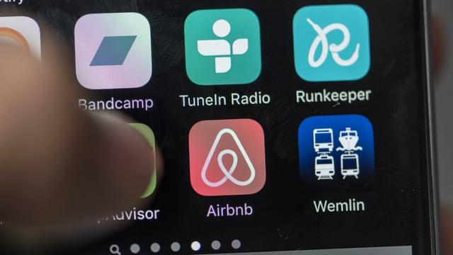 Daumen über Handybildschirm mit App-Symbolen