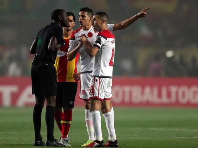 Die Spieler von Wydad Casablanca diskutieren mit dem Schiedsrichter.