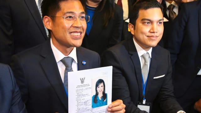 Der Chef der Partei Thai Raksa Chart (links) hält das Antragsformular von Prinzessin Ubolratana für die Parteimitgliedschaft in der Hand.