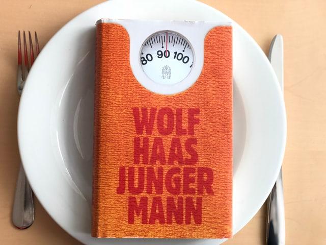 Der Roman «Junger Mann» von Wolf Haas liegt auf einem weissen Teller. Messer und Gabel daneben.