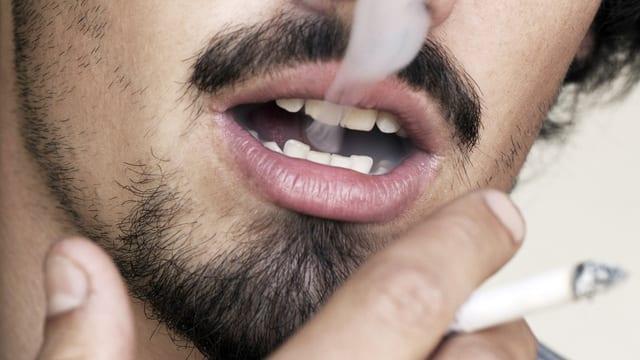 Mund eines Rauchers, aus dem Rauch steigt.