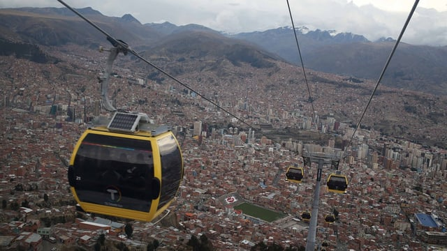 Gelbe Gondel von CWA vor der Skyline der Stadt La Paz