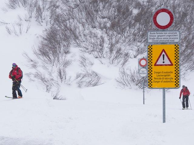 Zwei Personen laufen auf Skiern einen Hang hinauf.