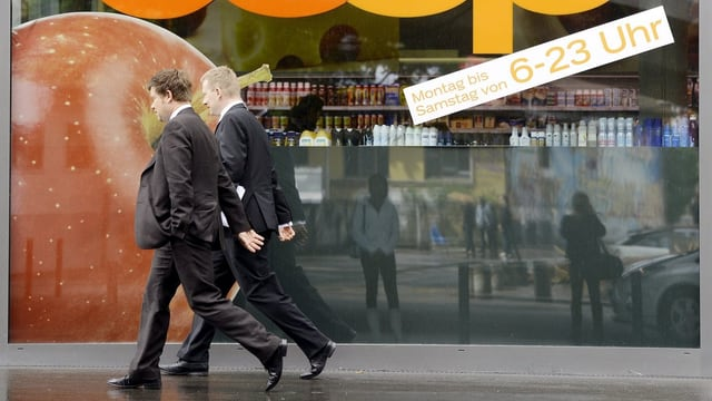 Personen gehen an einem Laden vorbei.