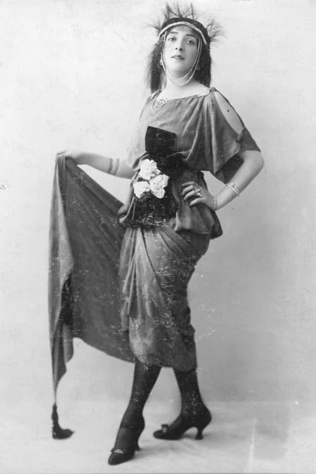 Frau in Kostüm mit wallendem Rock, Stiefeletten und Blumenbouquet um den Bauch gebunden.