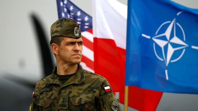 Ein polnischer Soldat vor der polnischen, US- sowie Nato-Flagge