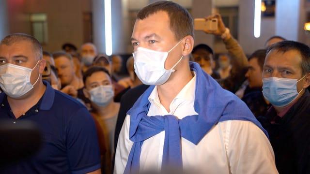 Mann mit Gesichtsmaske und einem blaumen Sweater über die Schultern gelegt.