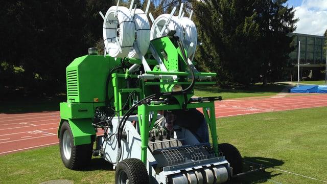 Eine grüne Maschine mit vier Rädern steht auf einem Stück Rasen. Oben auf der Maschine hat es viele Leitungen.