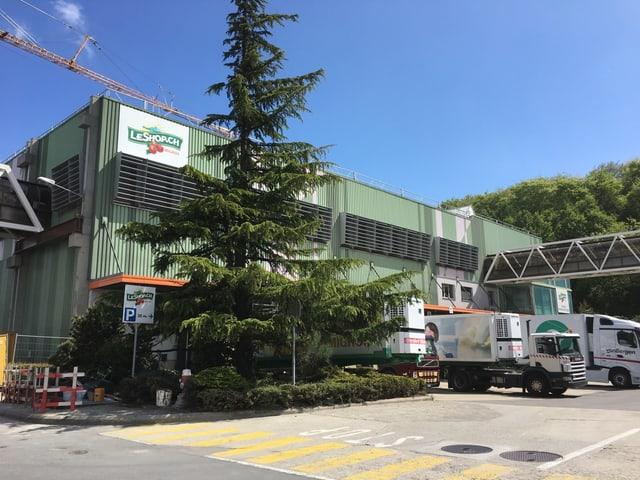 Vor dem grünen Lagergebäude von LeShop stehen ein paar parkierte Lastwagen.