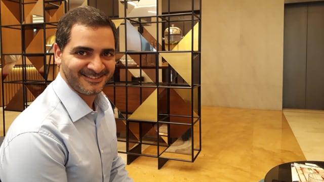 Ayman Mhanna, ein jümgerer Mann, sitzt auf einem Sesselhocker.
