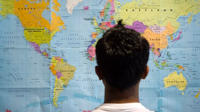 Asylbewerber schaut auf Weltkarte.