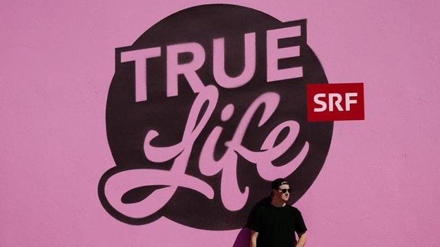 Das True Life Logo auf pinkem Hintergrund.