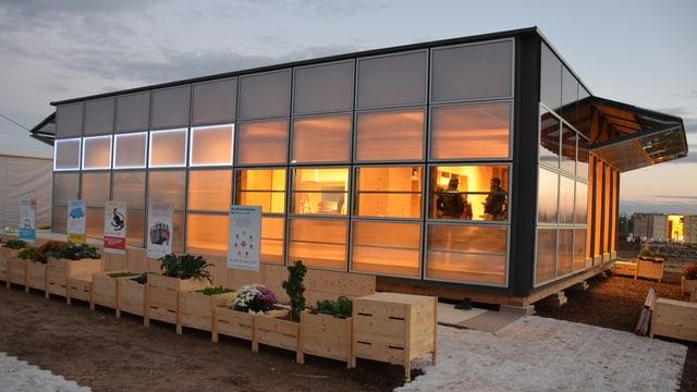 Haus mit Glasfassade, innen beleuchtet