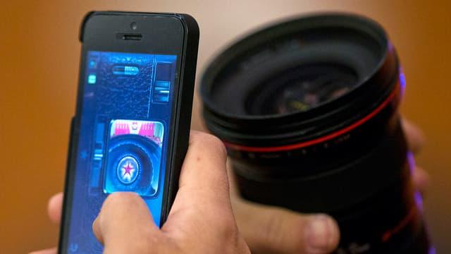 Eine Hand hält ein Smartphone, eine andere das Zoomobjekt einer Kamera.