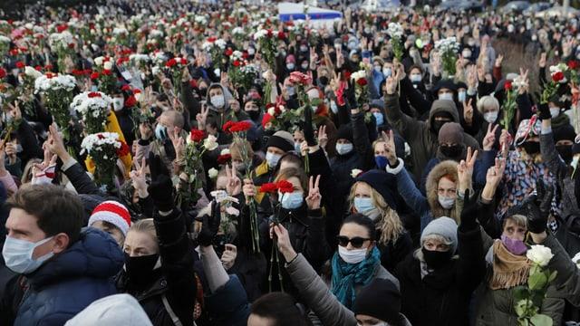 Hunderte Personen versammeln sich anlässlich der Beerdigung von Demonstrant Roman Bondarenko und machen zum Zeichen des Protests das Friedenszeichen