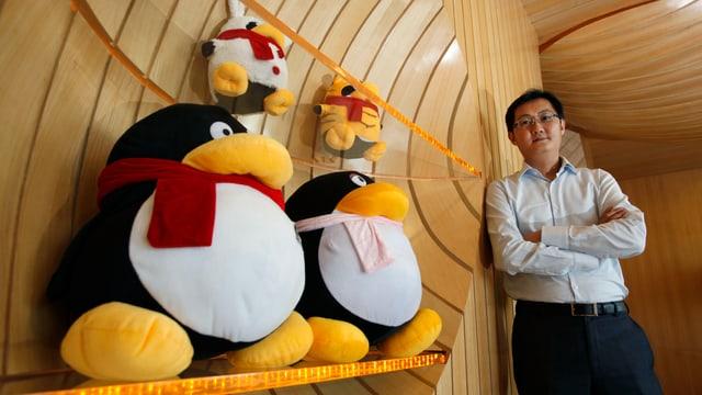 Portrait Pony Ma, neben ihm zwei Plüsch-Pinguine