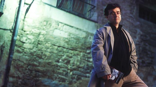 Javier Cercas in einer Gasse, bei Nacht, Trenchcoat, Buch unterm Arm