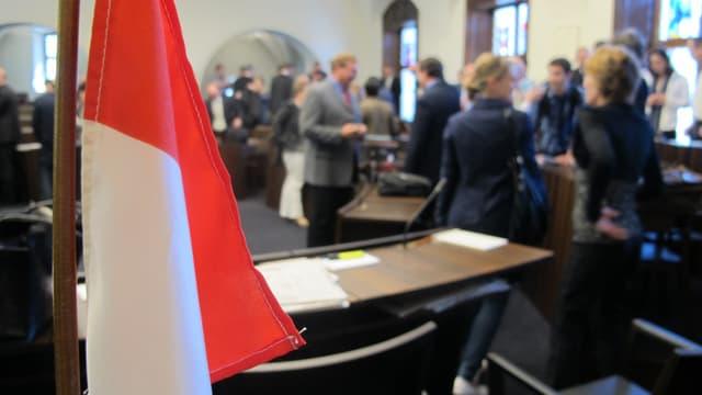 Blick in den Kantonsratssal Solothurn mit diskutierenden Personen unscharf im Hintergrund. Vorne eine Solothurn-Flagge.