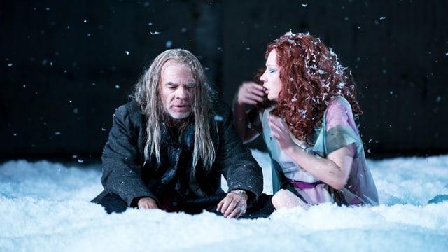 Eine Frau und ein Mann sitzen im Schnee.